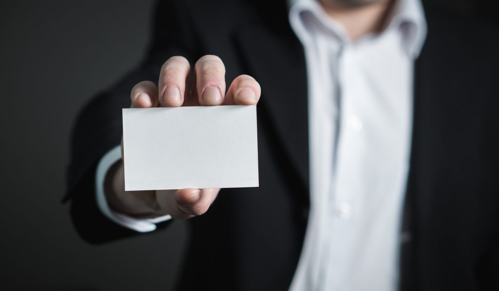Here's How To Determine The Perfect Career For You - man holding blank business card